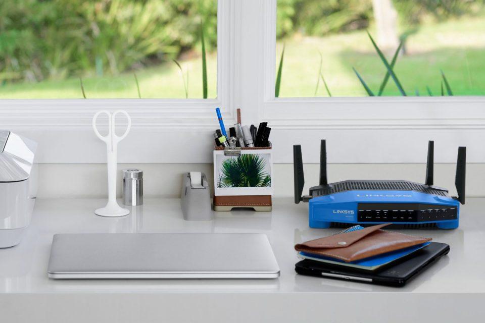 синий роутер на столе с ноутбуком